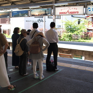 People standing in line waiting for the Enoshima Electric Railway